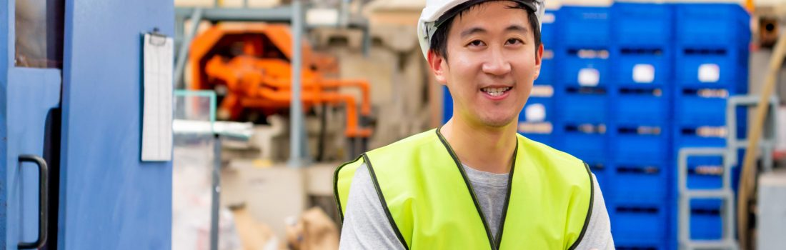 Front view of Asian factory worker with safety hard hat posed looking at camera with happy smile in industrial facilities at heavy industry manufacturing factory